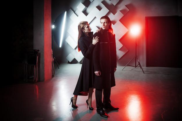 Пара в студии, портрет с резким светом и эффектом красного тонирования