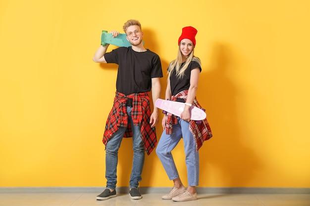 Пара в стильных футболках и скейтбордах возле цветной стены