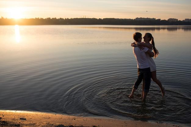 Пара в восходе солнца на пляже