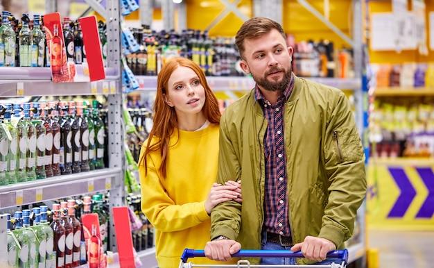 슈퍼마켓의 술 부서에있는 부부는 통로에서 병이있는 선반을보고 선택하십시오.
