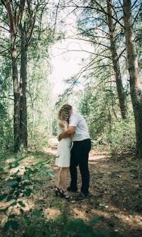 숲속의 남자와 소녀는 숲의 배경에 있는 큰 오래된 나무 아래에서 함께 포옹한다
