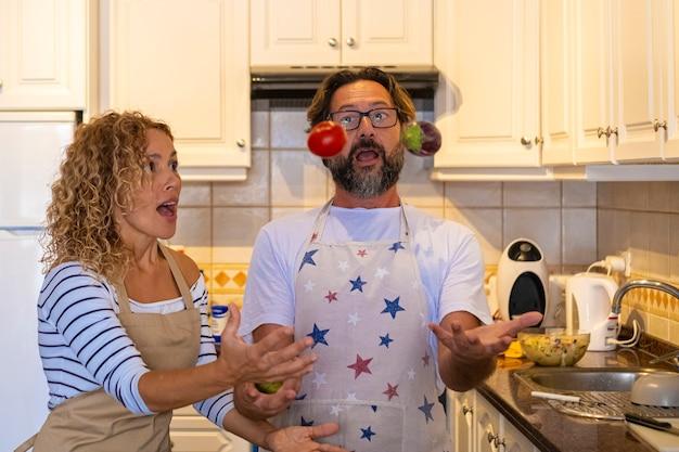 キッチンのカップルは、昼食の準備中に食べ物と一緒に遊んで面白い余暇の活動をしています。幸せな男性と女性は家で楽しんでいます