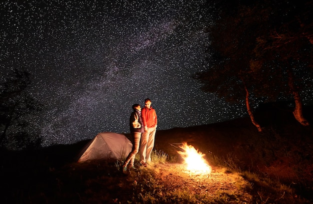 별이 빛나는 하늘 아래 불에 의해 산에서