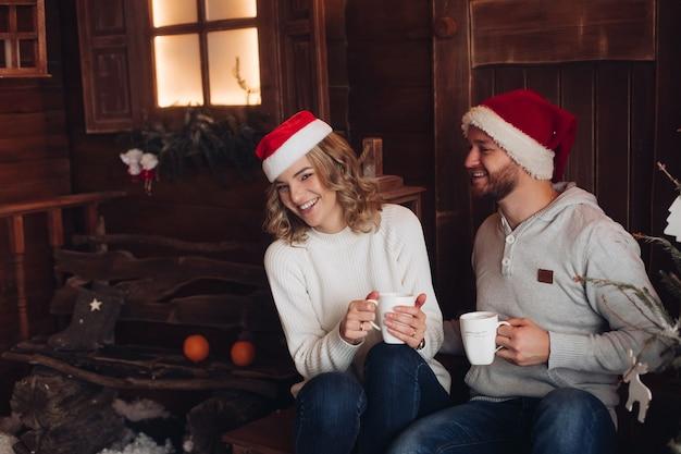 雪の降る天気で赤と白の帽子と同じ暖かい布でカップル