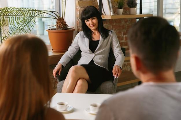 セラピーや結婚カウンセリングのカップル。心理学者、カウンセラー、セラピスト、または人間関係コンサルタントがアドバイスを提供します。心理療法のセッションに座っている男性と女性。家族、メンタルヘルスの概念。