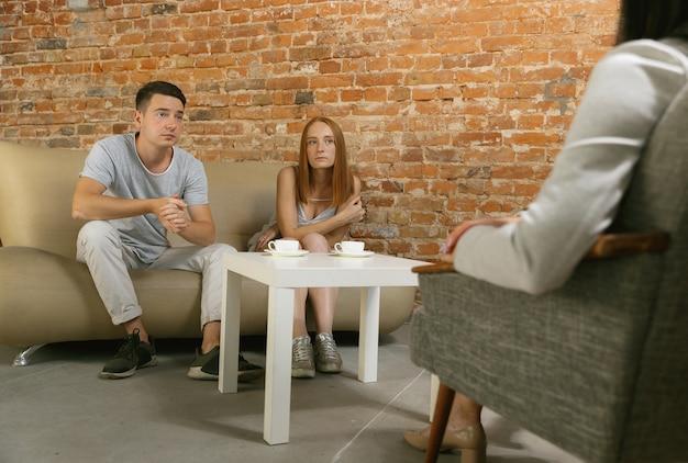 セラピーや結婚カウンセリングのカップル。心理学者、カウンセラー、セラピスト、または関係コンサルタントがアドバイスを提供します。心理療法のセッションに座っている男性と女性。家族、メンタルヘルスの概念。