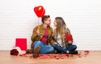 Couple in valentine day at indoors holding a heart symbol and balloons