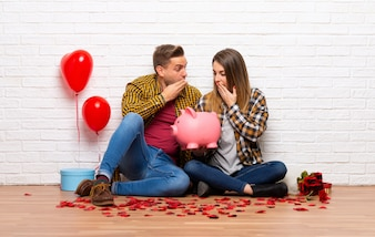 Couple in valentine day at indoors surprised while holding a piggybank