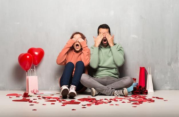 手で目を覆っているバレンタインデーのカップル