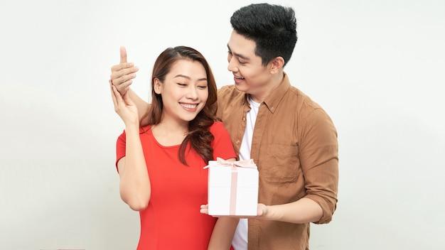 Пара в день святого валентина держит подарок на изолированном фоне, обнимая