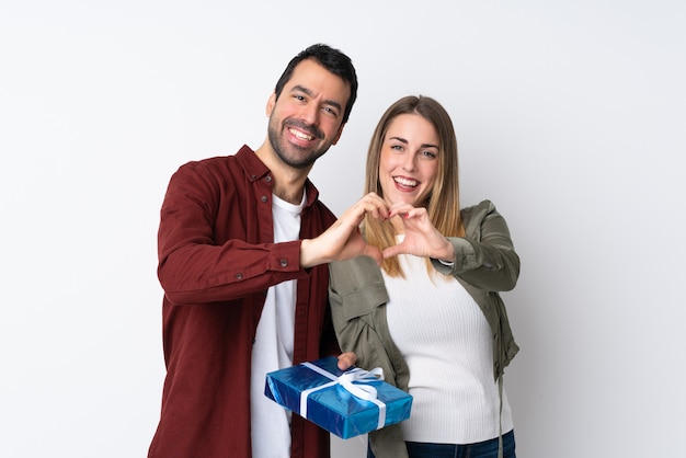 손으로 하트를 만드는 고립 된 벽 위에 선물을 들고 발렌타인 데이의 커플