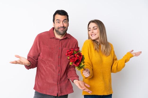 Пара в день святого валентина, держа цветы над изолированной стеной, имея сомнения, поднимая руки и плечи
