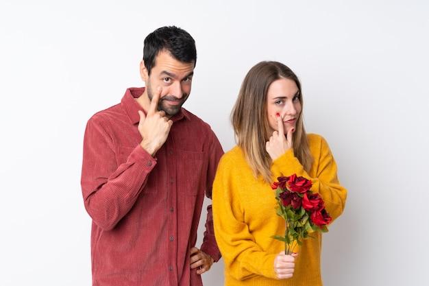 Пара в день святого валентина, держа цветы над изолированной стеной, глядя на фронт