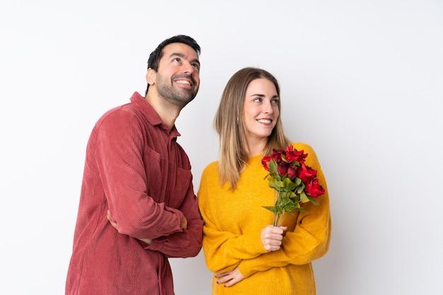 Пара в день святого валентина, держа цветы над изолированной стеной, глядя вверх, в то время как улыбается