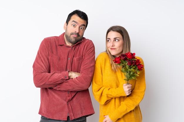 Пара в день святого валентина, держащая цветы по изолированной стене, делающей жест сомнения, поднимая плечи