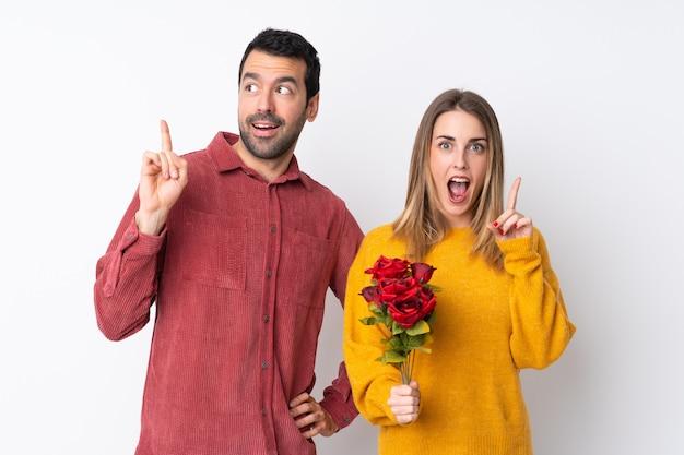 Пара в день святого валентина, держа цветы над изолированной стеной, думая, идея, указывая пальцем