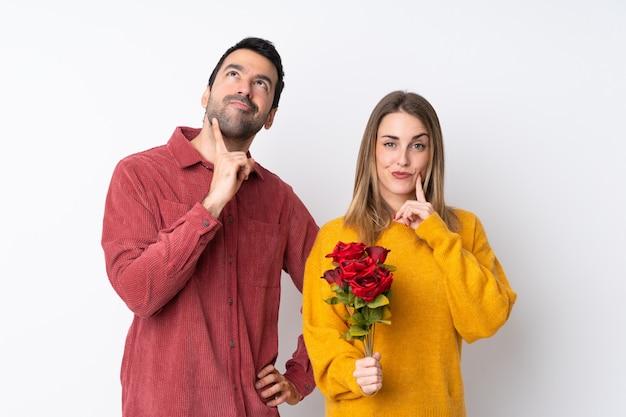 Пары в дне валентинки держа цветки над изолированной стеной думая идея пока смотрящ вверх