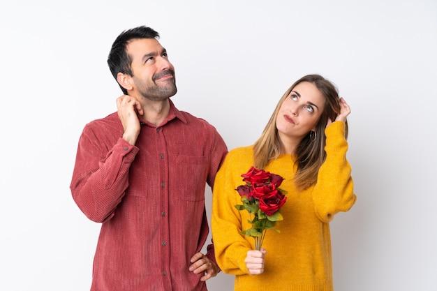 Пары в дне валентинки держа цветки над изолированной стеной думая идея пока царапающ голову