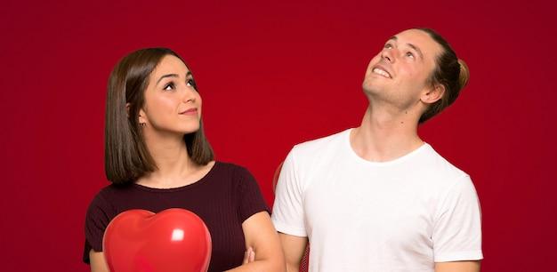 Пара в день святого валентина, глядя вверх, улыбаясь на красном фоне