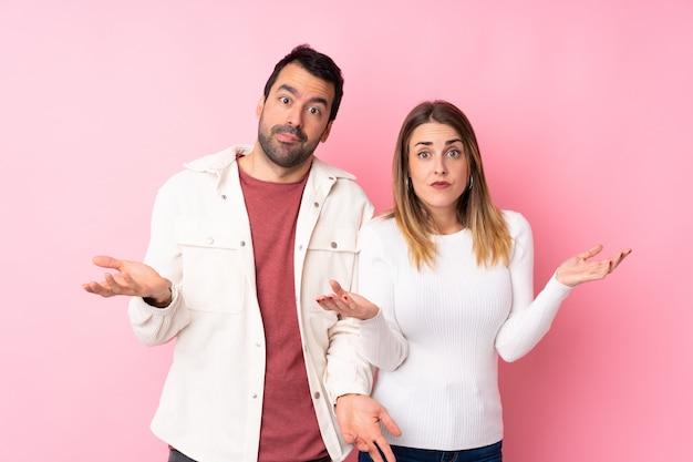 Пара в день святого валентина над изолированной розовой стеной, имеющей сомнения, поднимая руки и плечи