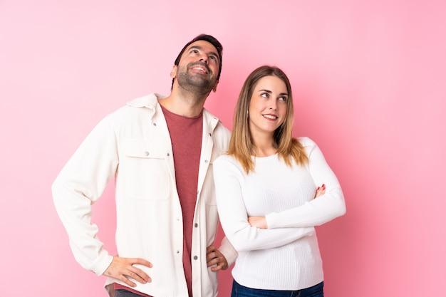 Пара в день святого валентина на изолированной розовой стене, глядя вверх, в то время как улыбается