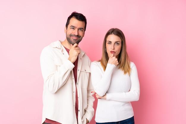 Пара в день святого валентина над изолированной розовой стеной, улыбаясь и глядя на фронт с уверенным лицом