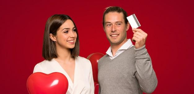 赤い背景の上に携帯電話でメッセージを送信するバレンタインデーのカップル