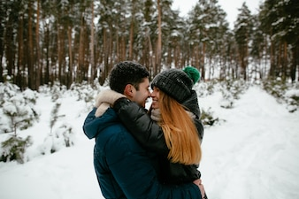 Couple in winter clothes walking in a snowy forest. Winter Love story.