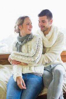 Пара в зимней одежде, сидящей против окна