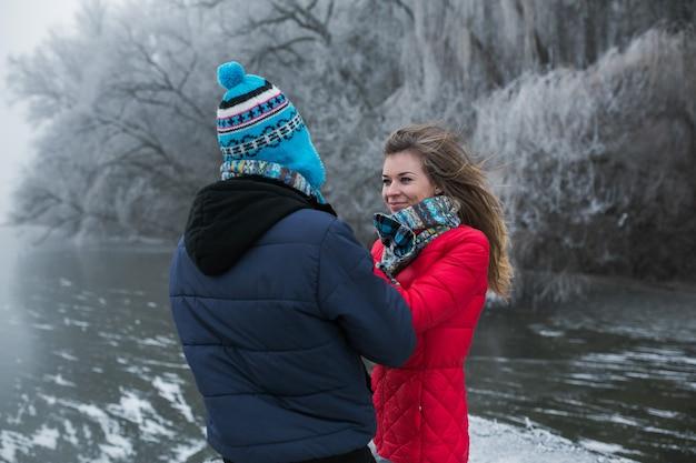 湖の近くの冬の森のカップル