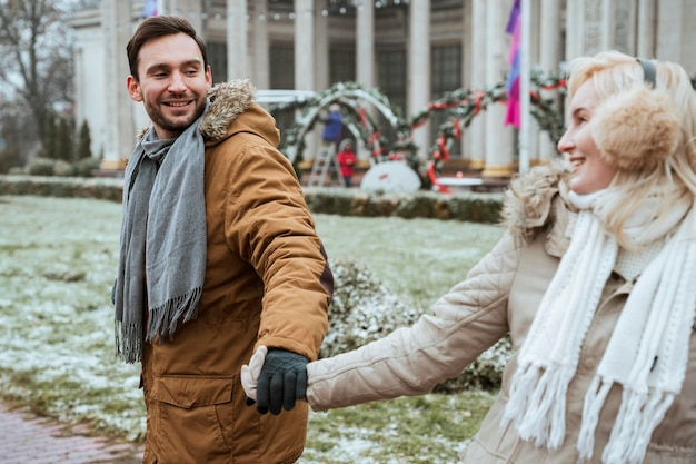 Пара зимой, взявшись за руки на открытом воздухе