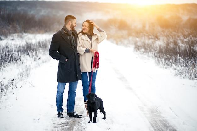 犬と一緒に通りの冬のカップル