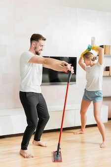 Couple indoors dancing with cleaning accessories