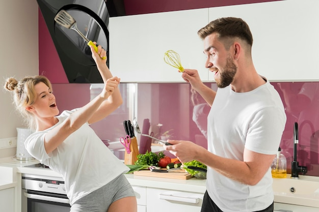 Couple indoors fooling around in the kitchen with objects