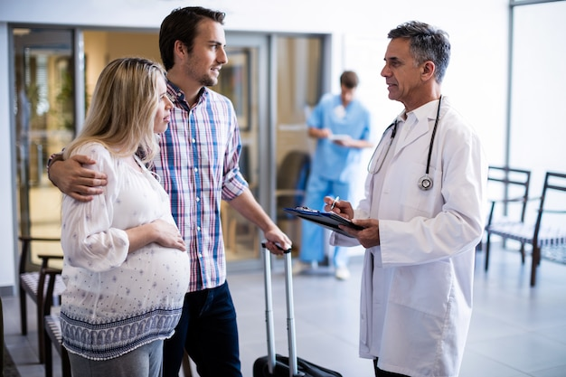 Couple interacting with male doctor in corridor