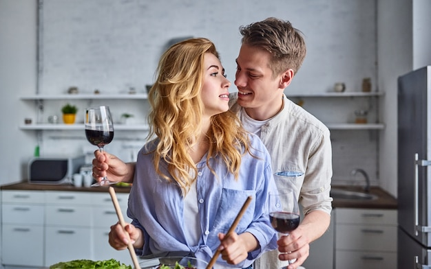 Пара готовит на кухне красивый мужчина и женщина веселятся вместе, делая салат