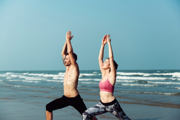 The couple is doing a yoga at the beach