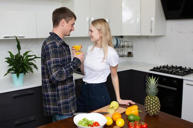 カップルは夕食を一緒に調理しながら家で一緒にフレッシュジュースを飲んでいます