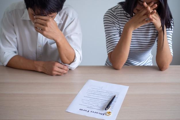 カップルは離婚証明書に署名することに同意した後、ストレスを感じています。家族の問題、離婚、喧嘩、葛藤を抱える恋人たちの概念