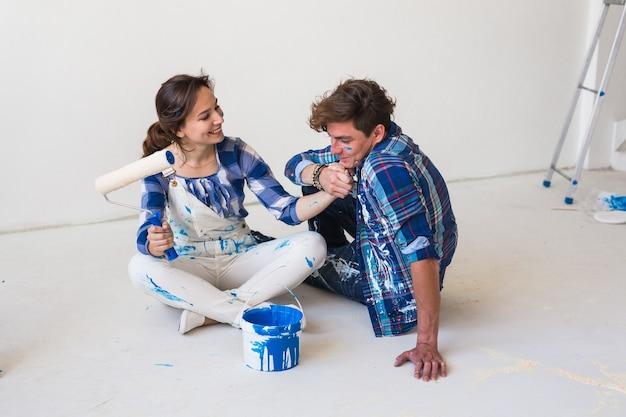 Пара собирается красить стены, выбирая цвет.