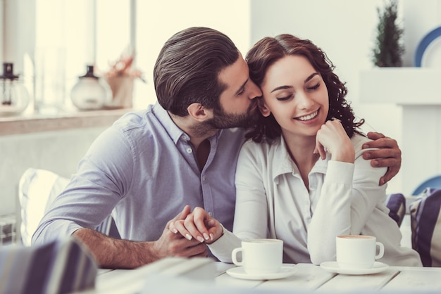 Couple is holding hands and smiling while resting in cafe.