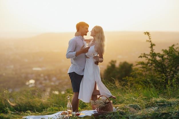 커플이 여름 피크닉에서 포옹하고 와인을 마시고 있다