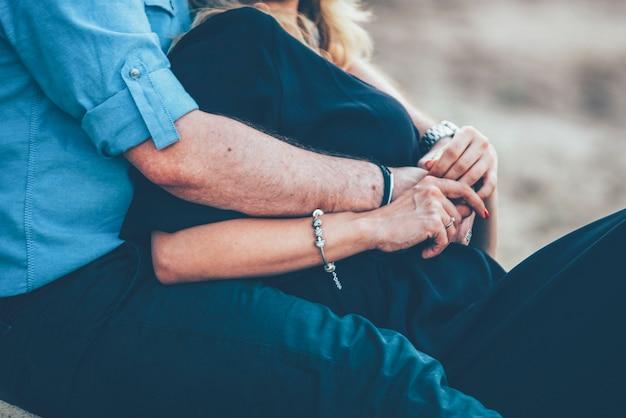 Пара обнимает и сидит близко руки
