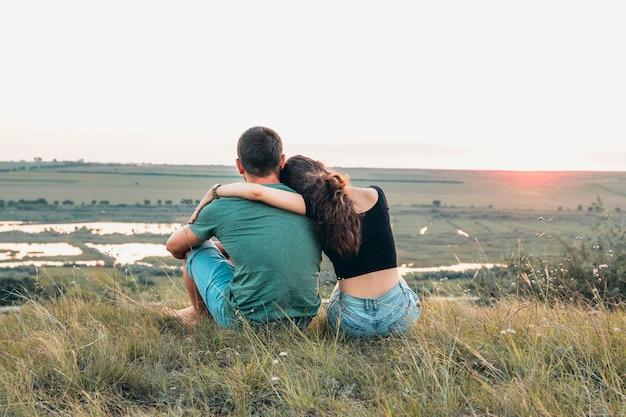 커플 포옹과 일몰 언덕에 가까이 앉아