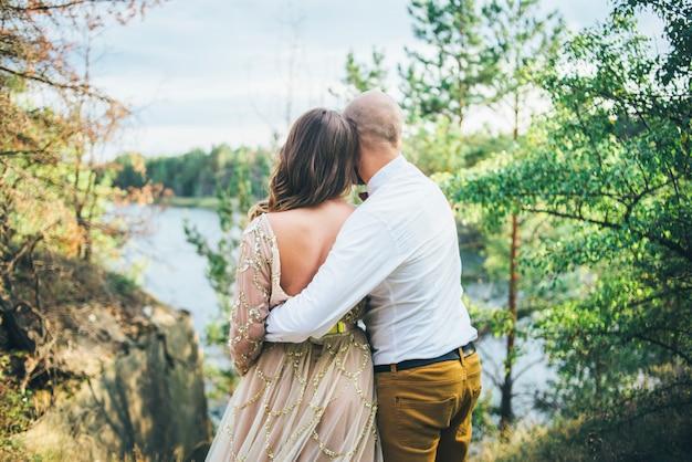 Пара обнимает друг друга и смотрит на природу