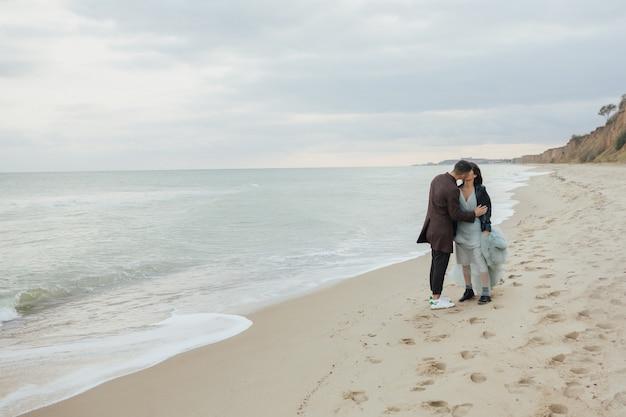 カップルはキスをし、海の海岸線を歩いています
