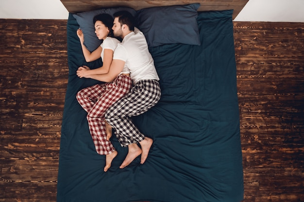 Couple is lying and sleeping on bed