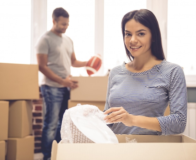 Couple is packing their stuff into the boxes ready to move