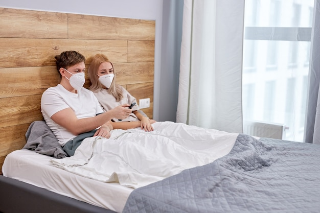 Couple is quarantined at home, watching tv, sitting on bed wearing medical masks, isolated because of the coronavirus quarantine covid-19, epidemic. side view