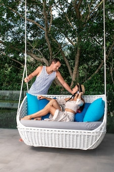 A couple is relaxing together on a garden swing